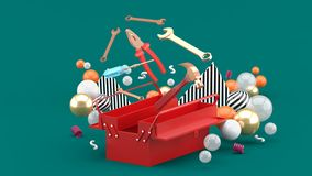 Toolbox amidst colorful balls on a green background royalty free stock photo
