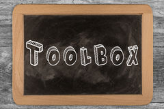 Toolbox - chalkboard with outlined text. On wood Royalty Free Stock Image