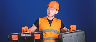 Toolbox and equipment concept. Worker, repairer, repairman, builder on thoughtful face choosing equipment for work. Man. In helmet, hard hat holds toolbox and royalty free stock images