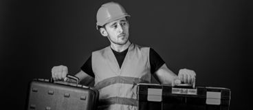Toolbox and equipment concept. Worker, repairer, repairman, builder on thoughtful face choosing equipment for work. Man. In helmet, hard hat holds toolbox and royalty free stock image