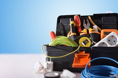 Toolbox full of tools and electrical equipment on white table stock photography