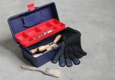 Toolbox med handskar och borsten Arkivbild