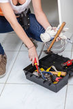 Toolbox. Woman Plumber looking a toolbox Royalty Free Stock Image