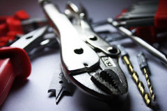 Tools 2. In the foreground brilliant flat-nose pliers and on back the scattered tools stock image