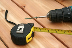 Tools. A drill and a tape measure on a new deck stock image