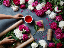 Tools and accessories florists need for making up a bouquet out of peonies: kraft paper, scissors, string, karkade tea royalty free stock image