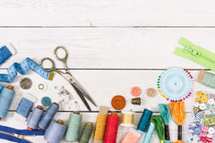 Tools and accessories for sewing on light wooden background. Stock Images
