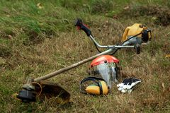 Free Tools And Equipment For Mowing Grass, The Lawn Lies On The Ground, A Grass Trimmer. Mowing Lawns, Roadsides, Mowing Grass Stock Images - 159688074