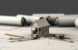 Tools of the architect and the wooden house on the sheets of dra. Wings. 3d illustration Royalty Free Stock Photo