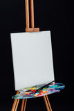 Tools of the artist. Brushes, wooden easel tripod, palette colorful. Black background, studio, nobody. Royalty Free Stock Photography