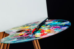 Tools of the artist. Brushes, wooden easel tripod, palette colorful. Black background, studio, nobody. Stock Image