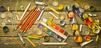 Tools for the artist. Objects for drawing. Paint, crayons, pencils on a wooden table. Inspiration to create. Top view. Flat lay royalty free stock photography