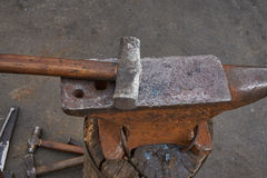 Tools of the blacksmith are an anvil and a hammer Stock Photo