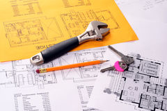 Tools on Blueprints including monkey wrench, keys. And monkey wrench House plans printed on white and yellow paper royalty free stock photo