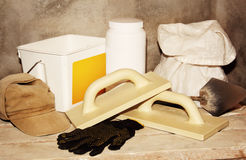 Tools and building materials for repairs. Trowel, gloves, cap, coat and other for priming and plastering walls