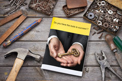 Tools Business Brochure Key Success. A tools workbench with brochure, pencil, hammer, nails and screws in old tin boxes Stock Photography