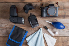 Tools for cleaning camera with dslr camera and lens, flash. Different objects on wooden background royalty free stock photos