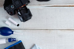 Tools for cleaning camera with dslr camera on white wood background. Selective focus Royalty Free Stock Photography