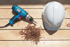Tools for the construction of a wooden floor or terrace. Screwdriver, self-tapping screws and helmet on the wooden floor Stock Photos