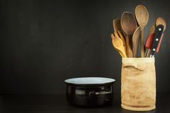 Tools cook on a wooden shelf. Kitchen utensils in a ceramic container on black background. Royalty Free Stock Images