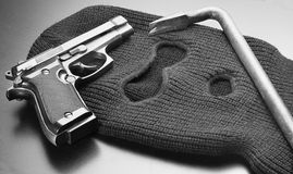 Tools of crime. Handgun and crowbar lying on mask, ready for being used for crime stock photo