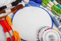 Tools for cross stitch. A hoop for embroidery and canvas on white canvas background. Mockup for hobby. Embroidery process with royalty free stock photos