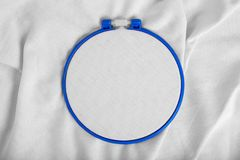 Tools for cross stitch. A hoop for embroidery and canvas on white canvas background. Mockup for hobby stock image