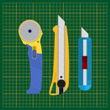 Tools for cutting paper and fabric. Stationery knife, cutting mat, rotary blade cutter. Stock Photo