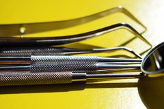 Tools for dental treatment on a yellow background royalty free stock photo