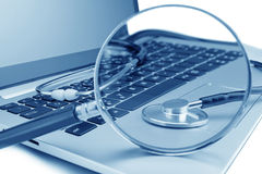 Tools for diagnostics on the laptop. Through a magnifying glass royalty free stock photo