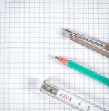 Tools for drawing and measuring. On a sheet in a cage Royalty Free Stock Images