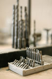 Tools drill bit on wooden work table. Close up of tools drill bit on wooden work table Royalty Free Stock Photos