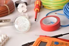 Tools and electrical material on a white table elevated view stock image