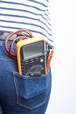 Tools for electrician in back pocket of blue jeans worn by a woman. Multimeter. Royalty Free Stock Image