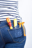 Tools for electrician in back pocket of blue jeans worn by a woman. Screwdriver, cutters and sharp knife. Stock Photos