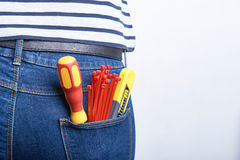 Tools for electrician in back pocket of blue jeans worn by a woman. Screwdriver, sharp knife and zip ties. Royalty Free Stock Images