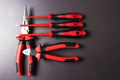 Tools electrician on a black background. Tool for working screwdriver, pliers, platypuses. Stock Photo
