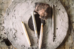 Tools for forming clay with pots on wood background Stock Photo