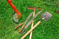 Tools for garden care. Manual electric lawn mower, shovel, rake, machete, scissors. Trim the green lawn. Garden care royalty free stock photo