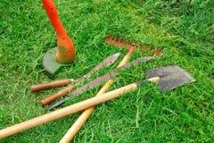 Tools for garden care. Manual electric lawn mower, shovel, rake, machete, scissors. Trim the green lawn. Garden care stock photos