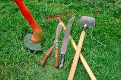 Tools for garden care. Manual electric lawn mower, shovel, rake, machete, scissors. Trim the green lawn. Garden care stock image