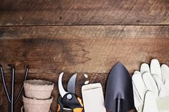 Tools of Gardening Background. Background of various gardening tools, gloves and vegetable seeds shot from above over a rustic wood table in flat lay style Stock Photo