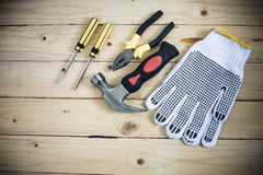 Tools and gloves on wooden table Stock Images
