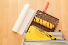 Tools for gluing wallpapers. Renovation. Tools for gluing wallpapers. A room after renovation. Fresh repair in a room. Floor from laminate Stock Photos