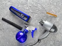 Tools for haircuts and hair care on a gray concrete background. Clippers, hair dryer, comb, spray. Top view stock images