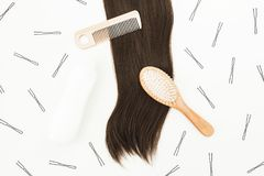 Tools for hairdresser with shampoo and hairs on white background. Flat lay, top view. Tools for hairdresser with shampoo and hairs on white background. Flat lay stock photography