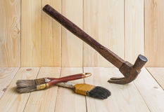 Tools, hammer and paint brush  on wood background Stock Image