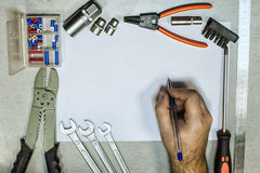 Tools and hand with a ballpoint pen. Which draws on paper Royalty Free Stock Photo