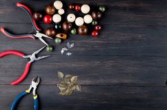 Tools for handmade jewelry. Beads, plier and wire. Tools for handmade jewelry. wooden Beads, plier and accessories to create hand made fashion jewelry on dark stock images