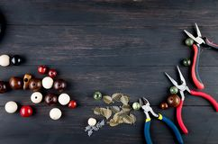 Tools for handmade jewelry. Beads, plier and wire. Tools for handmade jewelry. wooden Beads, plier and accessories to create hand made fashion jewelry on dark stock photography